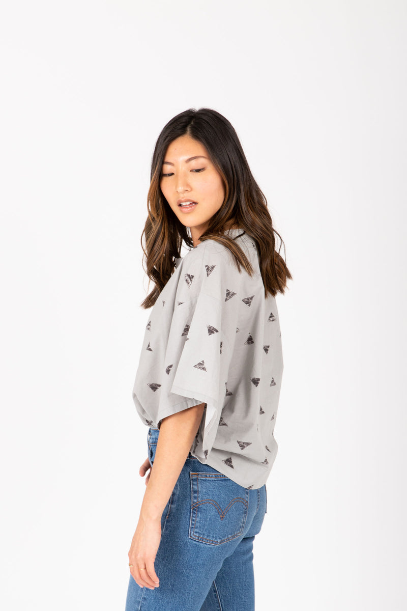 The Breck Triangle Blouse in Light Grey, studio shoot; side view
