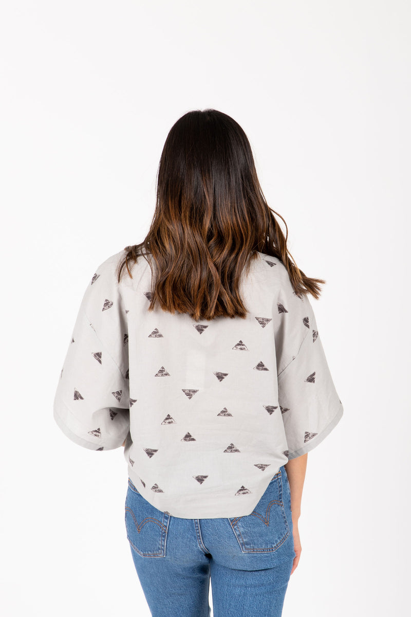The Breck Triangle Blouse in Light Grey, studio shoot;  back view