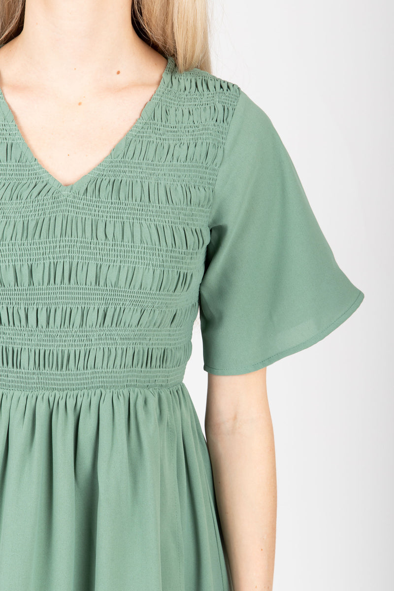 The Fancy Flutter Sleeve Dress in Sage, studio shoot; closer up front view