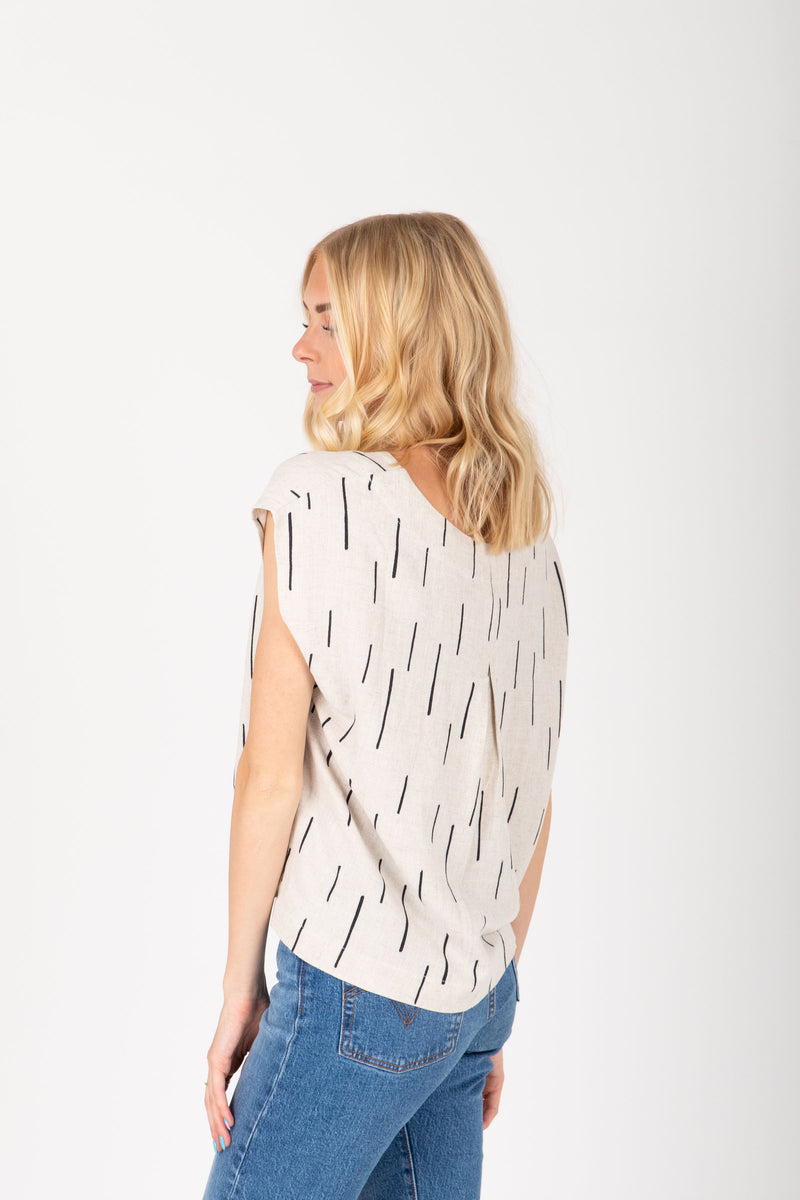 The Pepper Dash Linen Blouse in Natural, studio shoot; back view
