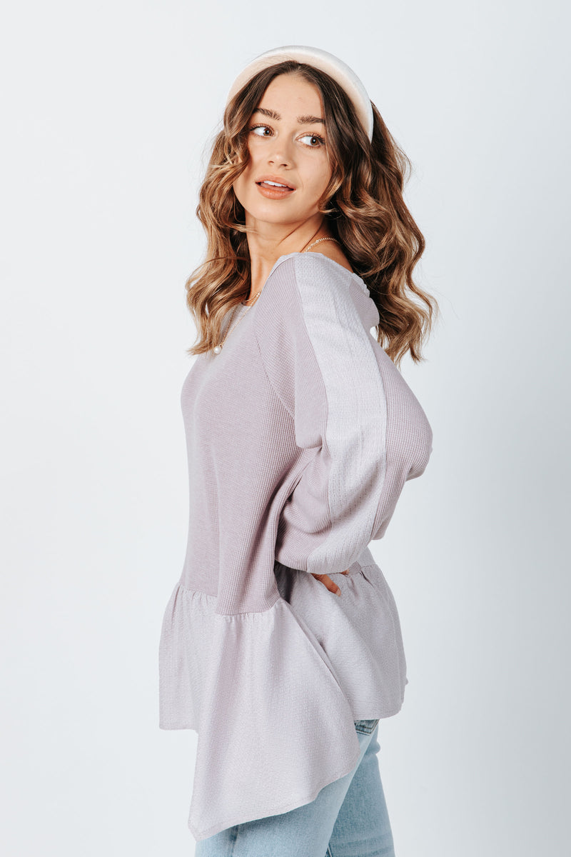 The Clive Peplum Blouse in Lavender, studio shoot; side view