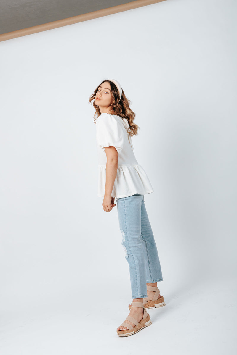 The Bailey Babydoll Blouse in Ivory, studio shoot; side view