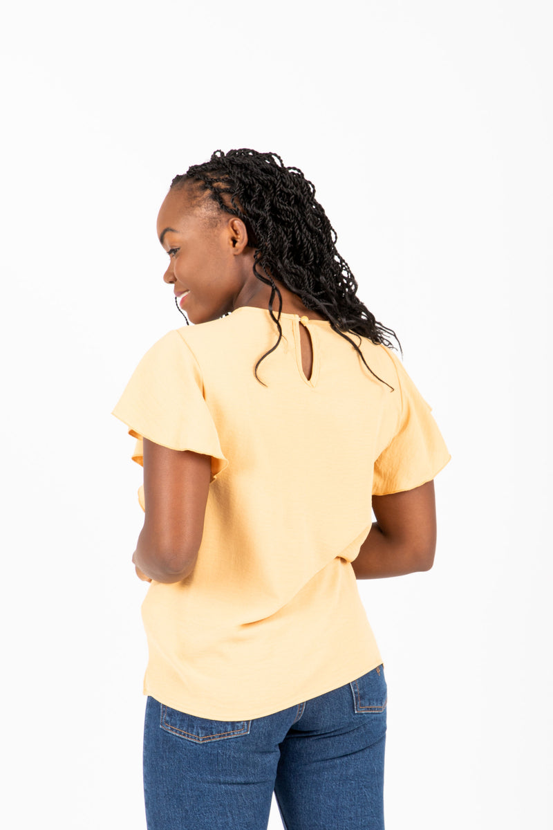 The Drake Embroidered Blouse in Mustard, studio shoot; back view