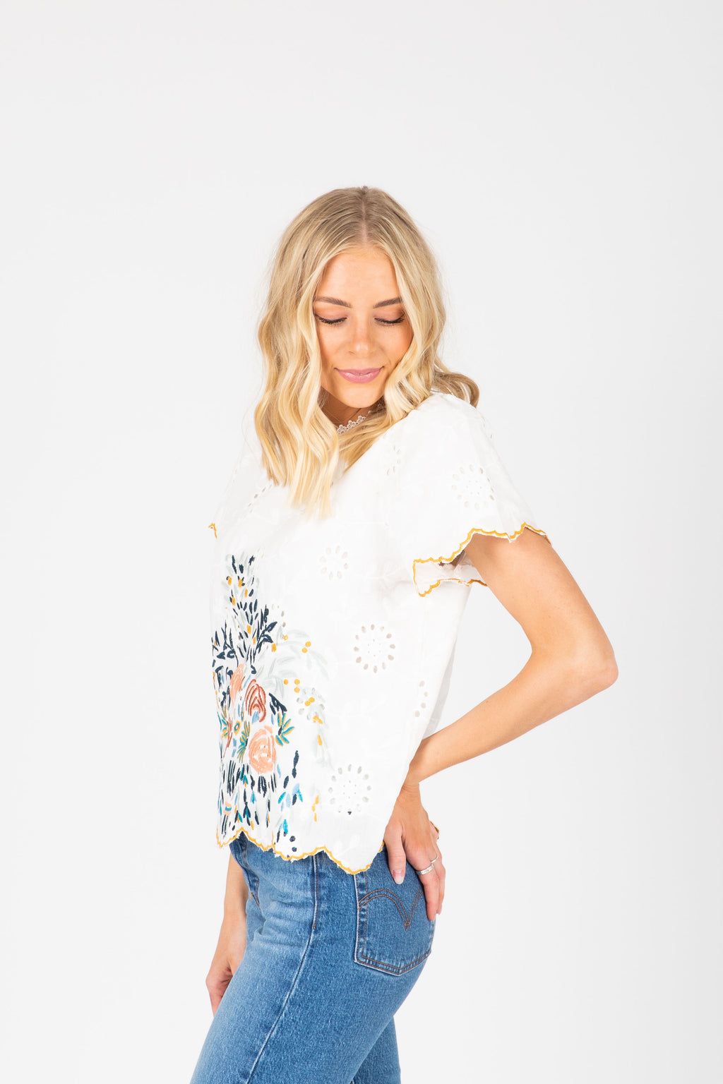 The Alessia Embroidered Scallop Blouse in White, studio shoot; side view