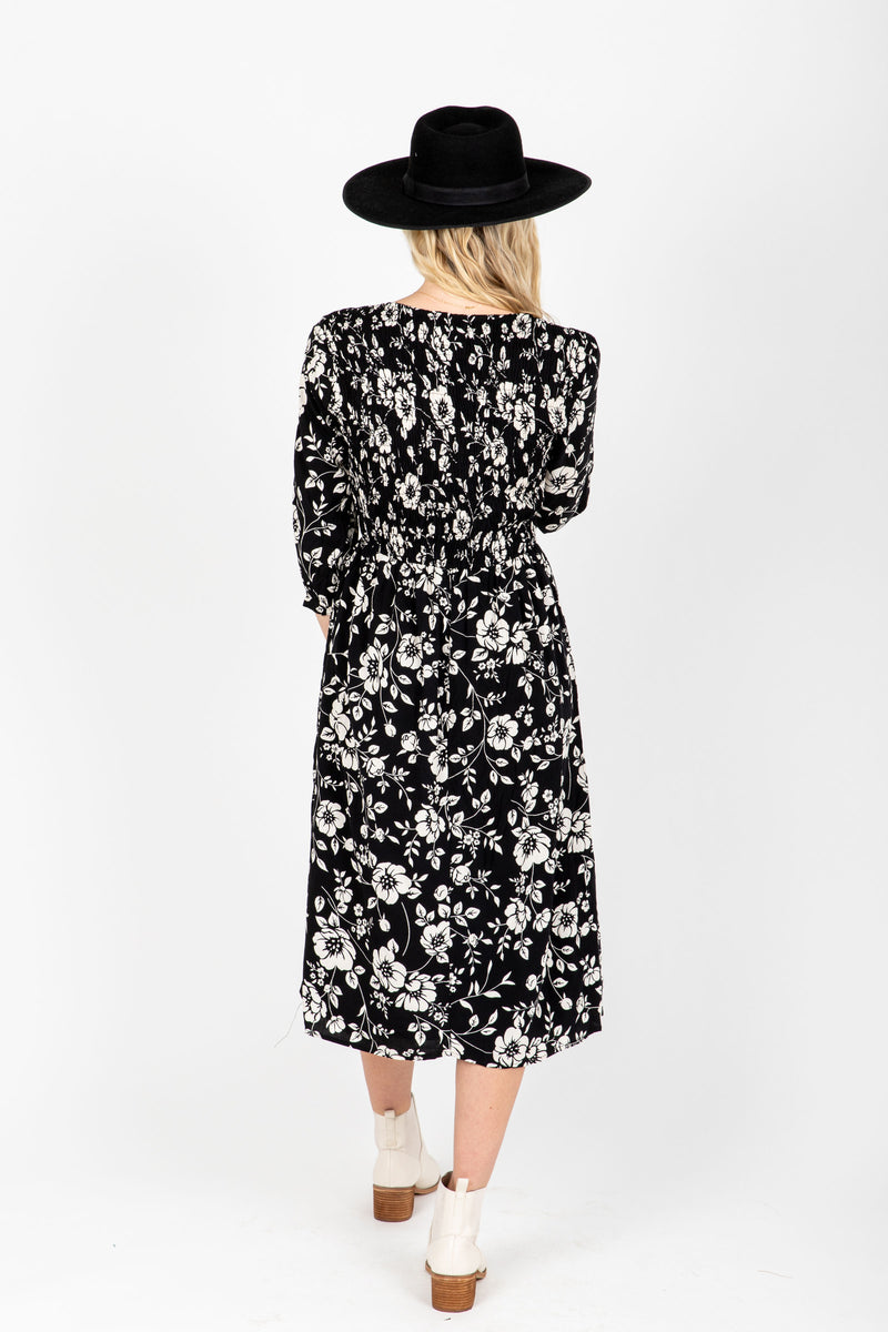 The Annie Smocked Floral Dress in Black, studio shoot; back view