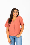 The Naya Scalloped Button Blouse in Brick, studio shoot; front view