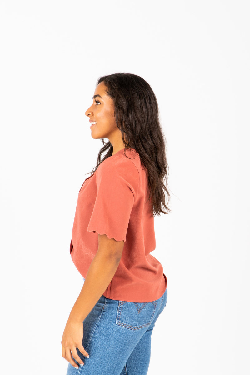 The Naya Scalloped Button Blouse in Brick, studio shoot; side view