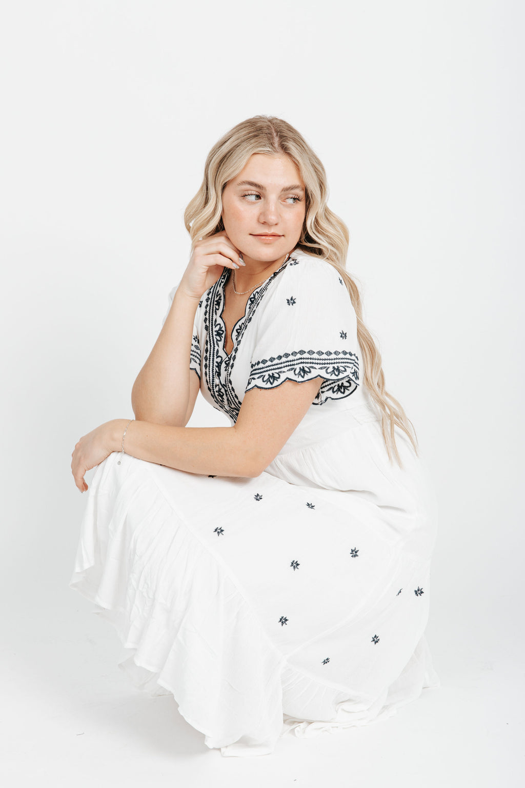 The Robin Embroidered Dress in White, studio shoot; side view