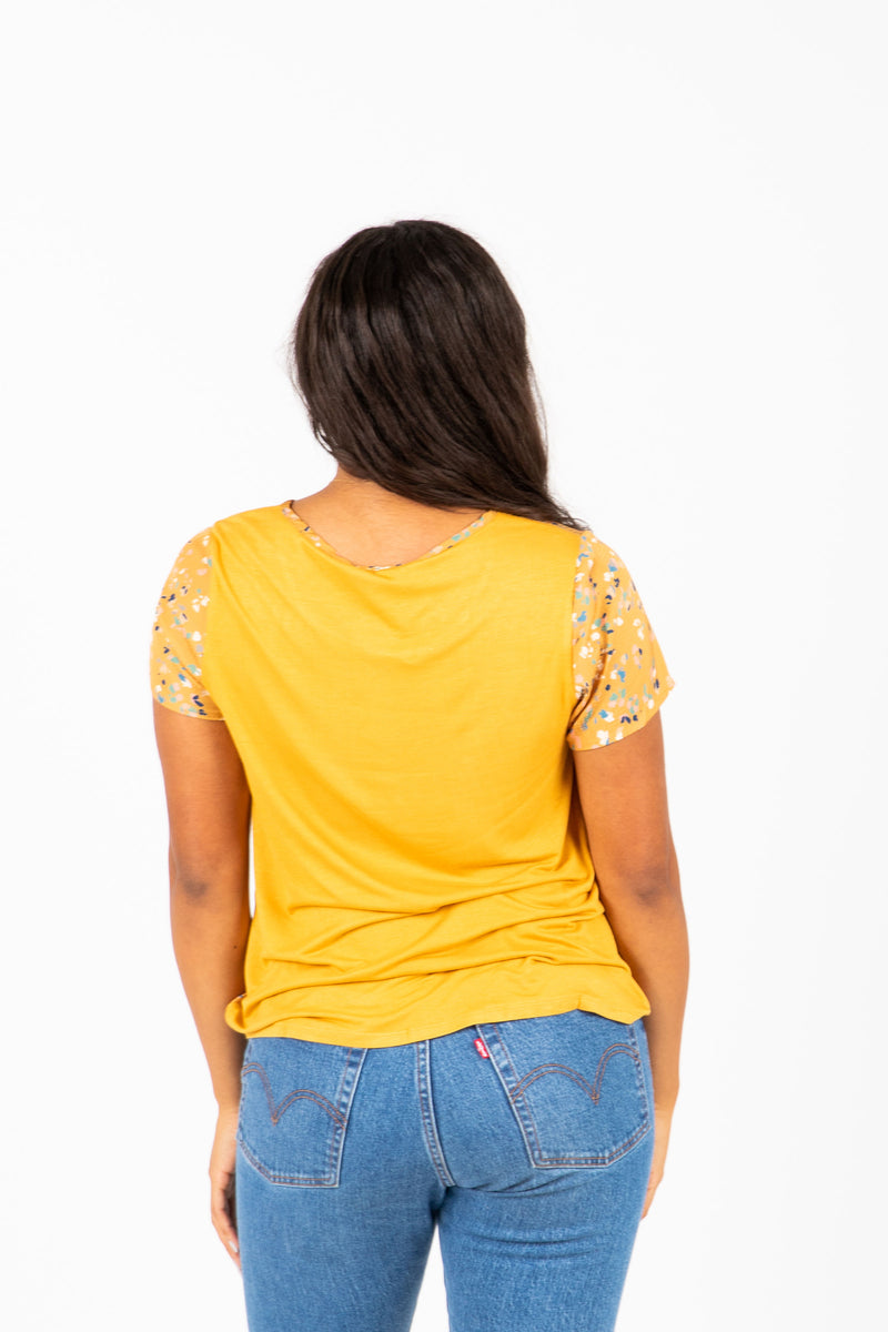 The Lovato Speckled Pleat Blouse in Mustard, studio shoot; back view