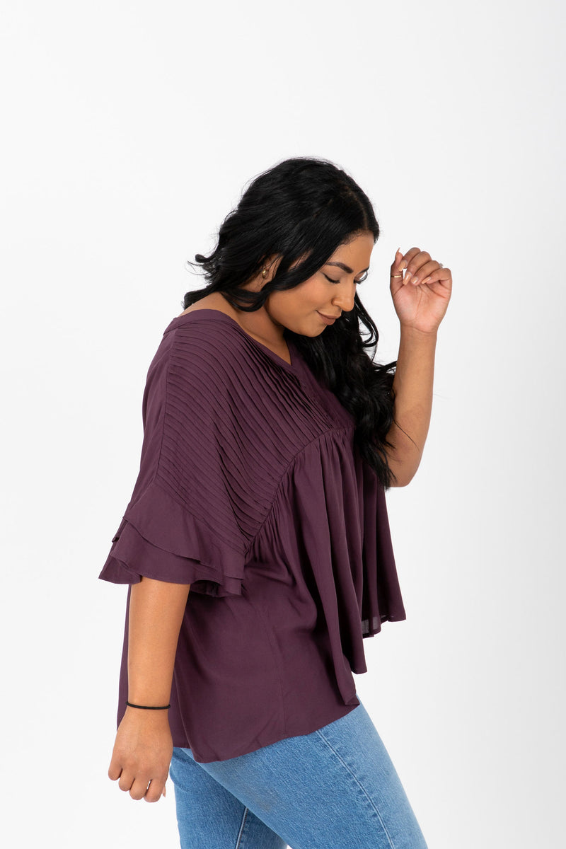 The Thora Pleated Empire Blouse in Burgundy, studio shoot; side view