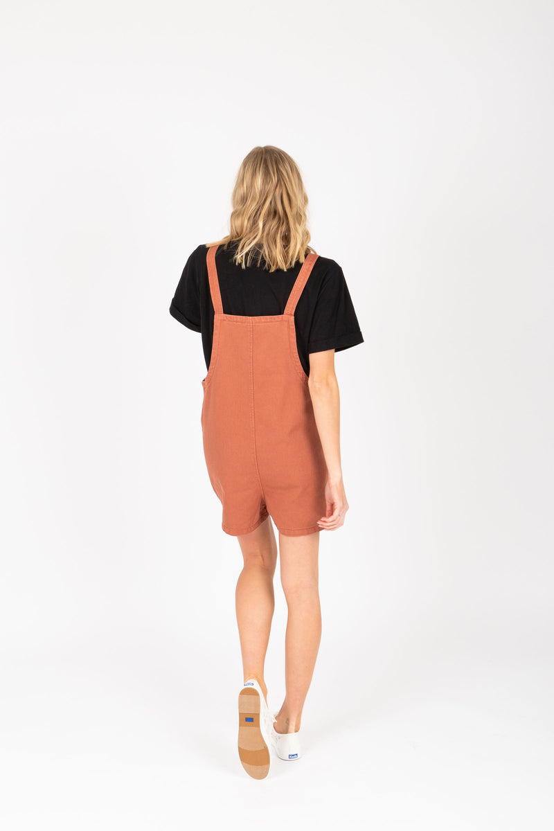 The Mina Shortie Overalls in Brick, studio shoot; back view