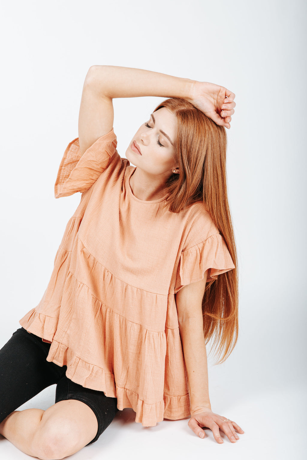 The Taylor Peplum Blouse in Peach, studio shoot; front view