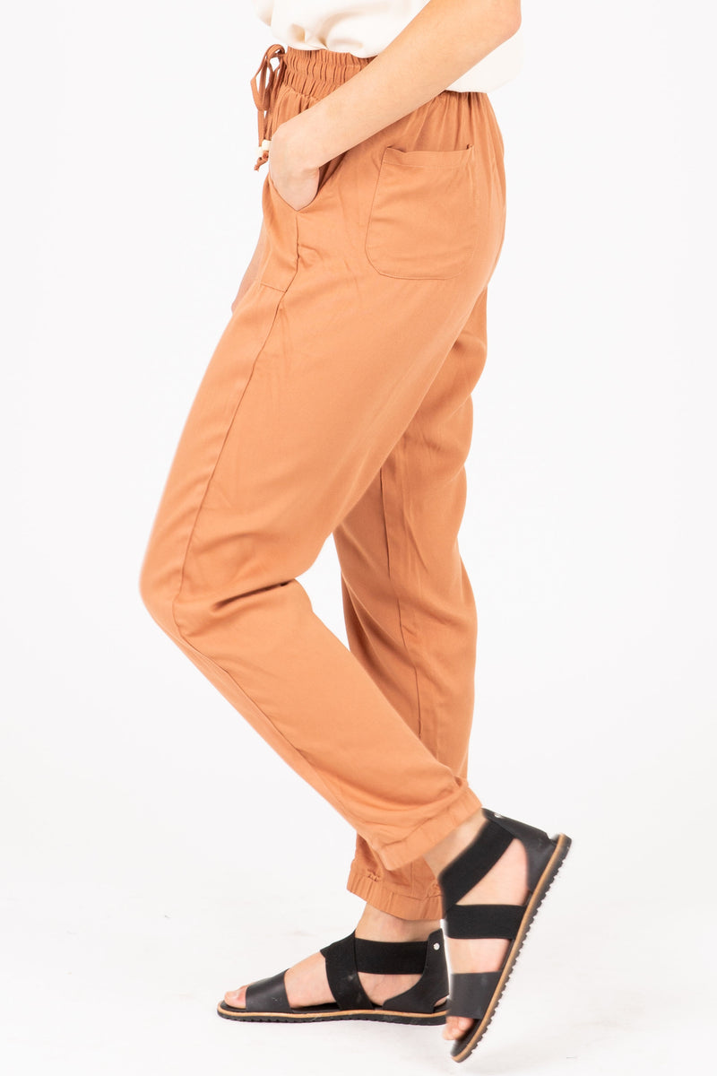 The Denver Tapered Trousers in Faded Brick, studio shoot; side view
