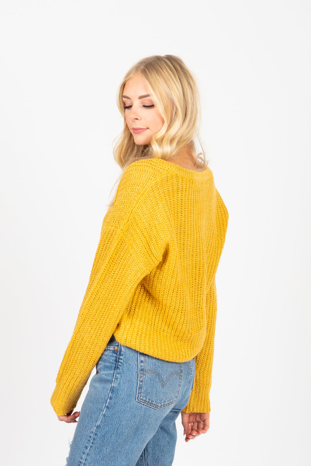 The Area Button Detail Sweater in Mustard, studio shoot; side view