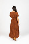 The Elise Patterned Wrap Dress in Rust, studio shoot; back view