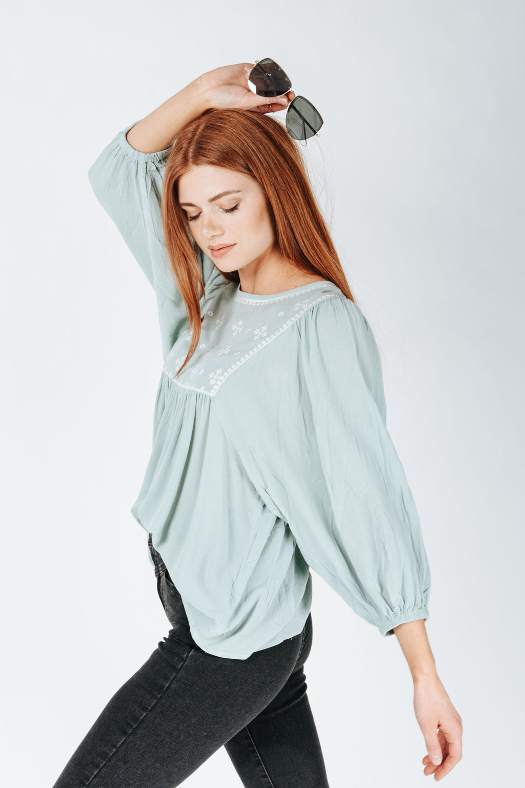 The Stafford Embroidered Babydoll Blouse in Sage, studio shoot; side view