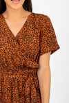 The Elise Patterned Wrap Dress in Rust, studio shoot; closer up front view