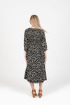 The Mena Dot Patterned Smocked Dress in Black, studio shoot; back view