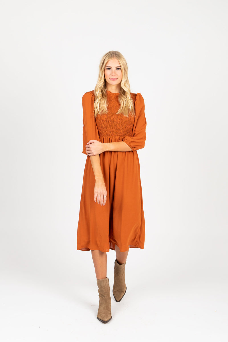The Ezra Smocked Midi Dress in Rust, studio shoot; front view