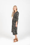 The Mena Dot Patterned Smocked Dress in Black, studio shoot; side view