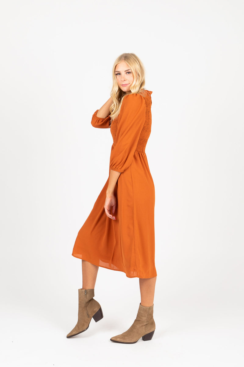 The Ezra Smocked Midi Dress in Rust, studio shoot; side view