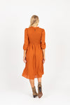 The Ezra Smocked Midi Dress in Rust, studio shoot; back view