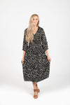 The Mena Dot Patterned Smocked Dress in Black, studio shoot; front view