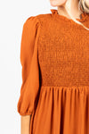 The Ezra Smocked Midi Dress in Rust, studio shoot; closer up front view