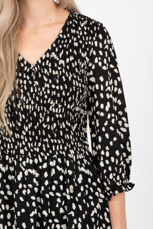 The Mena Dot Patterned Smocked Dress in Black, studio shoot; closer up front view