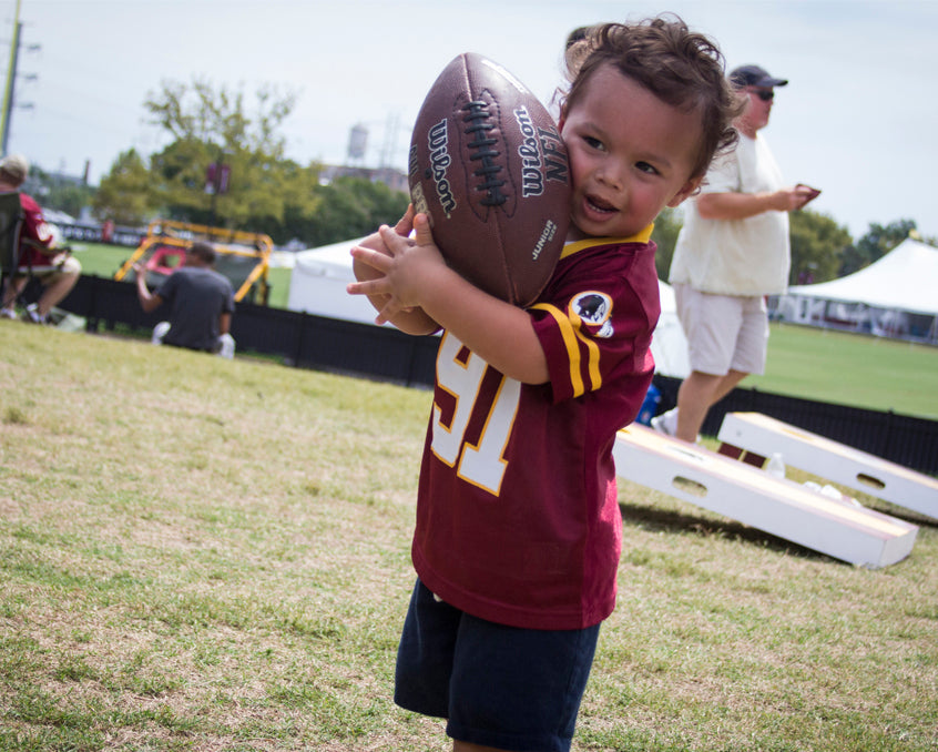 Toddler Redskins fan catching a football