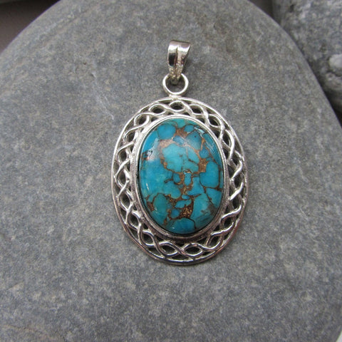 Sterling Silver Copper Turquoise Oval Pendant  features a turquoise stone set in a Celtic knot motif symbolizing the harmonious weaving together of two paths