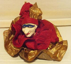 Harlequin jester ornament with blue mask, red and gold ruffle.