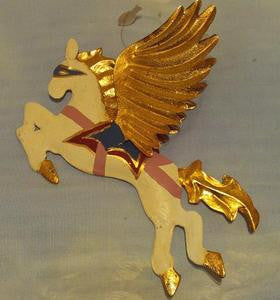 Pegasus ornament with gold wings/tail and pink/red harness.