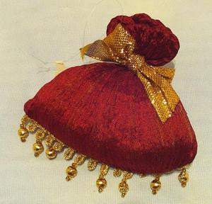 Red satchel ornament with gold bow and beaded trim.
