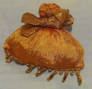 Gold satchel ornament with gold bow and beaded trim.