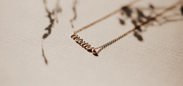 the story behind the mama script necklace
