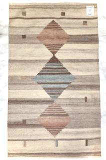 This hanwoven rug was made from recycled water bottles.  It has a background of brownish grey tones with thee diamonds, one being light blue and two a brownish mauve.