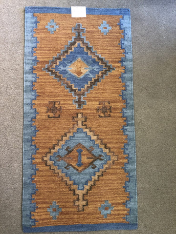 Rust and blue area rug that is handwoven.