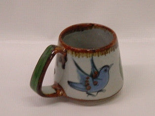 "Ken Edwards Truncated Mug 3.5""x5.5"" (T7) with brown rim.   It is natural grey clay color background with birds, butterflies, and leaves in blue, green, black and brown on the outside."