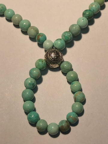 Light green/blue turquoise round bead with a Biuddhist central bead in sterling silver