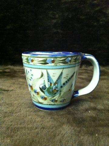Ken Edwards Collection coffee mug with blue rim.   It is natural grey clay color background with birds, butterflies, and leaves in blue, green, black and brown on the outside.