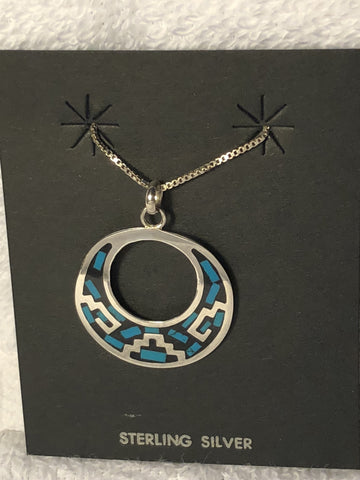 Sterling silver pendant with Aztec design and turquoise color inlay in black resin.