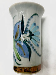 Ken Edwards stoneware vase with brown rim and bottom.  It is natural grey clay color background with birds, butterflies, and leaves in blue, green, black and brown on the outside.