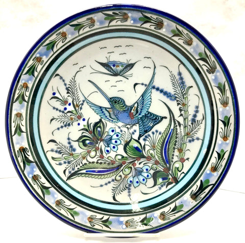Ken Edwards Colleciton series dinner plate with blue rim. It is natural grey clay color background with birds, butterflies, and leaves in blue, green, black and brown on the outside.