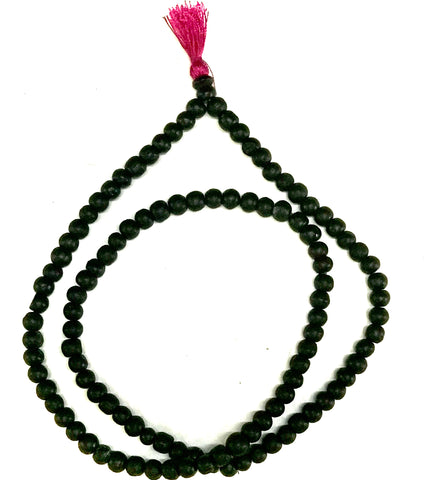 a string of black beads with a red tassle on the end.
