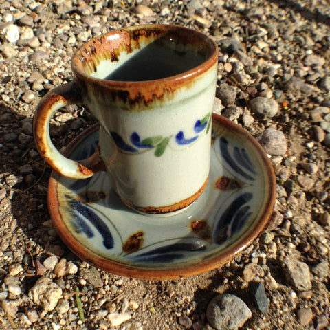 Ken Edwards Expresso cup and saucer set.  Brown rim on both pieces.  It is natural grey clay color background with birds, butterflies, and leaves in blue, green, black and brown on the outside.