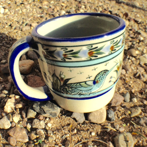 Ken Edwards Collection series coffee mug.   It is natural grey clay color background with birds, butterflies, and leaves in blue, green, black and brown on the outside.