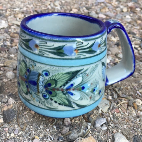 Ken Edwards Collection Series truncated coffee mug with  green, two shades of blue and brown flowers, birds, and butterflies decorated on the side or inside on bowls or plates