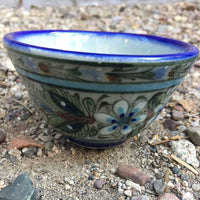 Ken Edwards collection series custard bown with blue rim.  It is natural grey clay color background with birds, butterflies, and leaves in blue, green, black and brown on the outside.