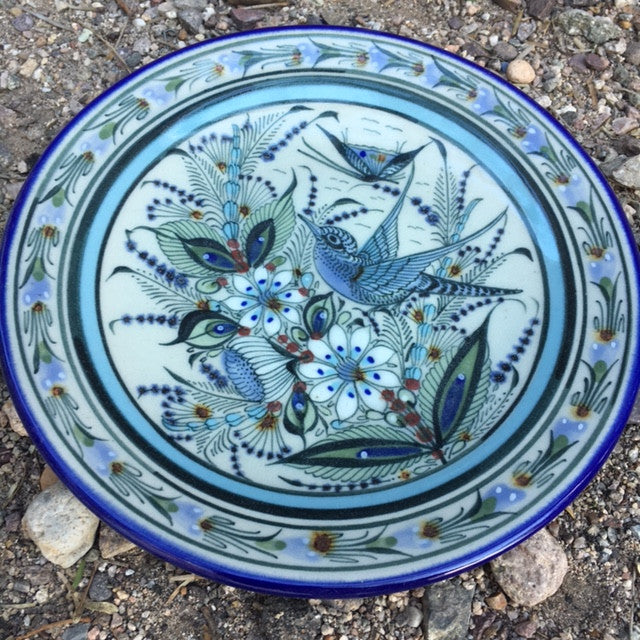 Blue rim Ken Edwards Collection series 8' salad plate .  It is natural grey clay color background with birds, butterflies, and leaves in blue, green, black and brown on the outside.